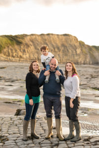 family on a stoney slate beach. Toddler on fathers shoulders.