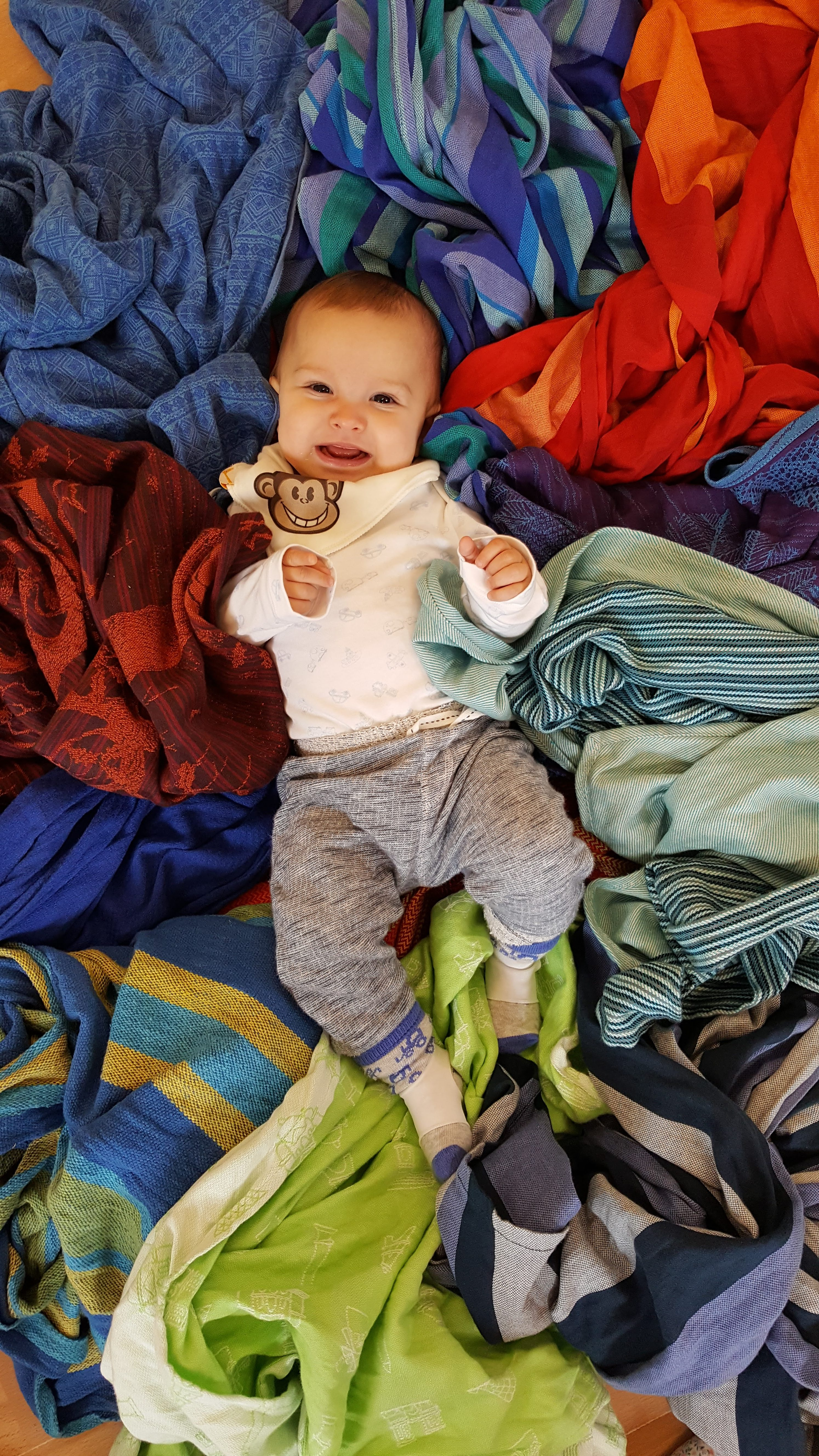 white baby aged 5 months, smiling on a pile of woven wraps